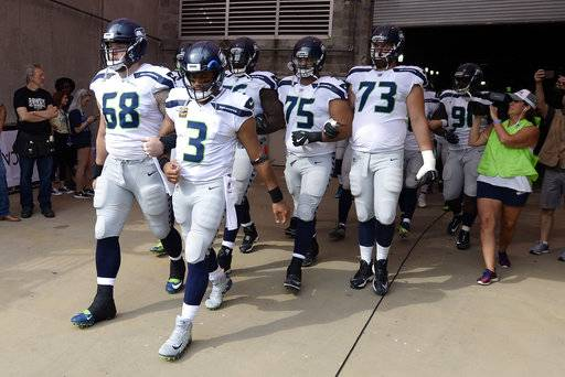 Seattle Seahawks quarterback Russell Wilson (3) and center Justin Britt (68) walk to the field with arms linked after the national anthem had been played before an NFL football game between the Seahawks and the Tennessee Titans Sunday, Sept. 24, 2017, in Nashville, Tenn. Neither team was present on the field for the playing of the anthem. (AP Photo/Mark Zaleski)The Associated Press