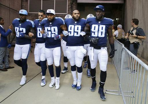 Tennessee Titans players walk to the field with arms linked after the national anthem had been played before an NFL football game between the Titans and the Seattle Seahawks Sunday, Sept. 24, 2017, in Nashville, Tenn. Neither team stood on the field for the anthem. From left are Delanie Walker (82), Marcus Mariota (8), Wesley Woodyard (59), Jurrell Casey (99) and Brian Orakpo (98). (AP Photo/James Kenney)The Associated Press