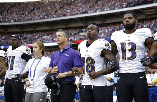 Baltimore Ravens head coach John Harbaugh, center left, links arms with his daughter Alison and wide receiver Jeremy Maclin (18) during the playing of the U.S. national anthem before an NFL football game against the Jacksonville Jaguars at Wembley Stadium in London, Sunday Sept. 24, 2017. Also pictured are Breshad Perriman (11) and Chris Matthews (13).
