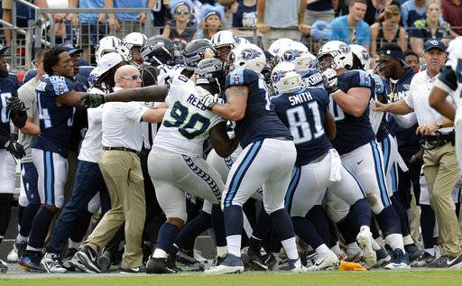 Tennessee Titans and Seattle Seahawks players fight after Seattle Seahawks cornerback Richard Sherman hit Tennessee Titans quarterback Marcus Mariota while out of bounds in the first half of an NFL football game Sunday, Sept. 24, 2017, in Nashville, Tenn.