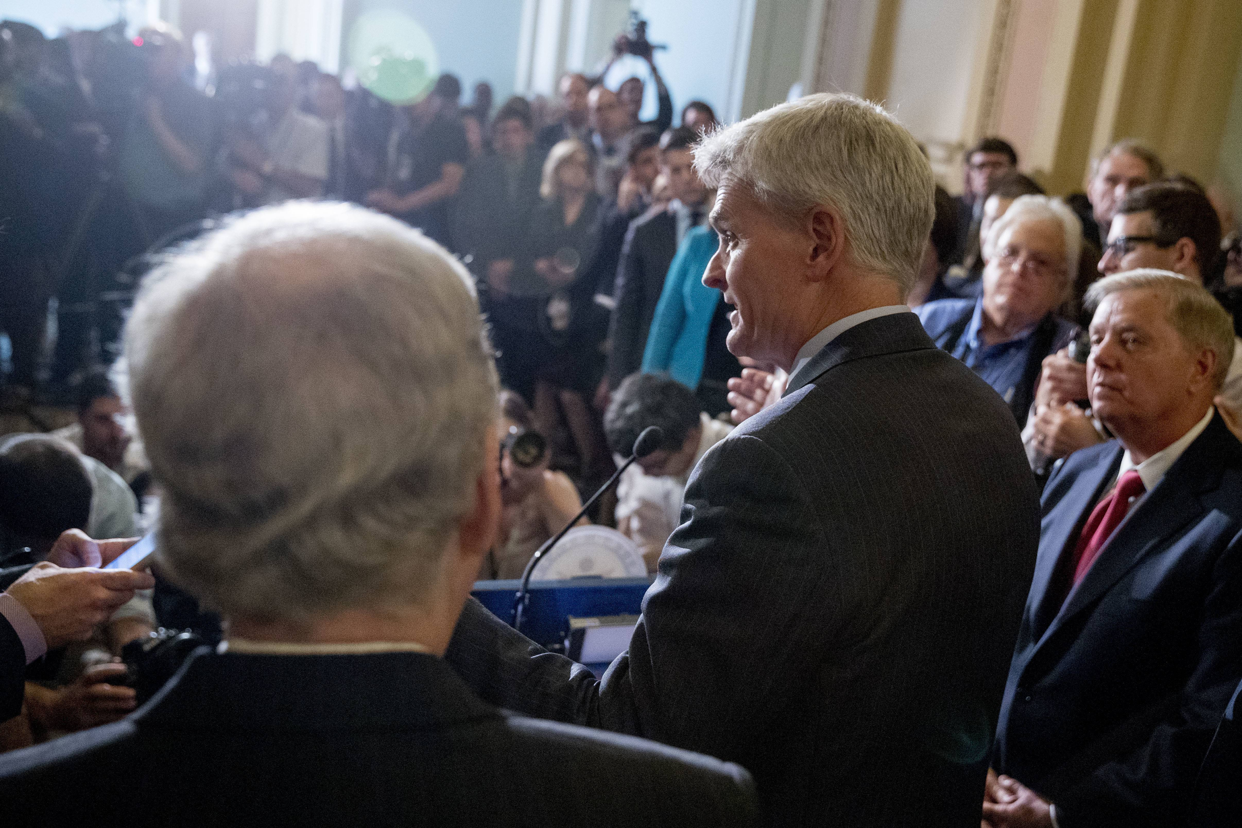 Sen. Lindsey Graham of South Carolina, flanked by Sen. Bill Cassidy of Louisiana, left, and Senate Majority Leader Mitch McConnell of Kentucky, right, speaks to reporters as Republicans faced assured defeat on the Graham-Cassidy bill, the GOP's latest attempt to repeal the Affordable Care Act on Tuesday in Washington, D.C. The decision marked the latest defeat on the issue for President Donald Trump and Senate Majority Leader Mitch McConnell in the Republican-controlled Congress.