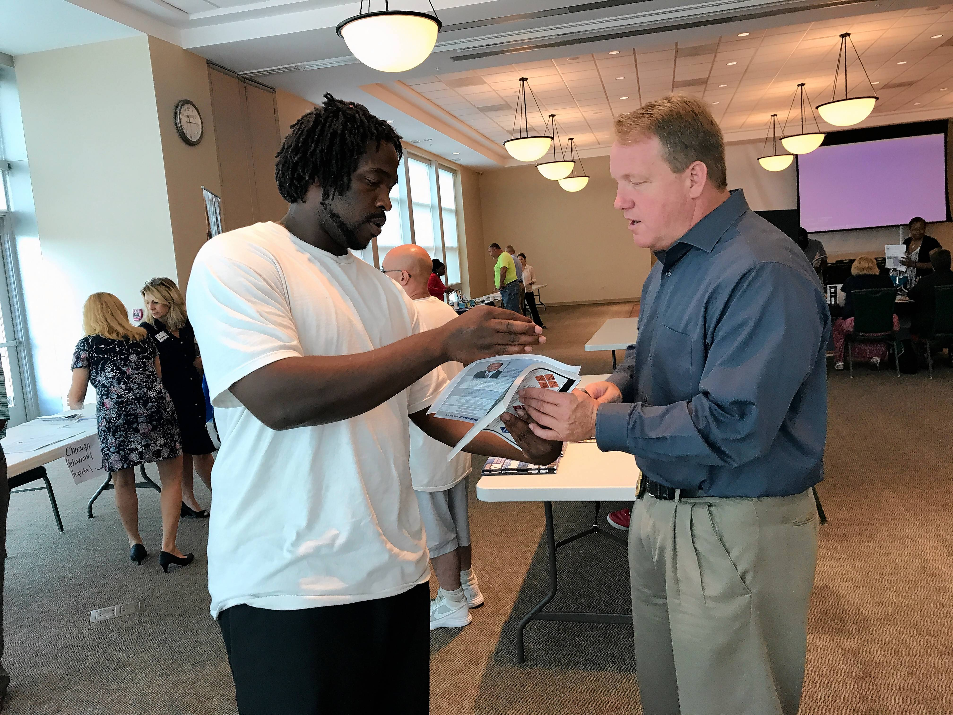 At a Re-Entry Collaborative meeting, Elgin police Lt. Rick Ciganek, right, gives his cellphone number to Jermaine Jones, a parolee staying in a halfway house.