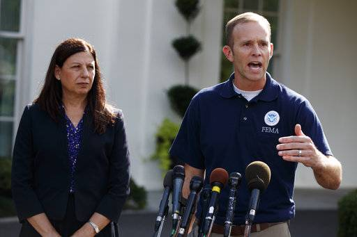 Acting Secretary of Homeland Security Elaine Duke, left, looks on as FEMA administrator Brock Long speaks to reporters about hurricane recovery efforts in Puerto Rico, outside the White House, Tuesday, Sept. 26, 2017, in Washington.