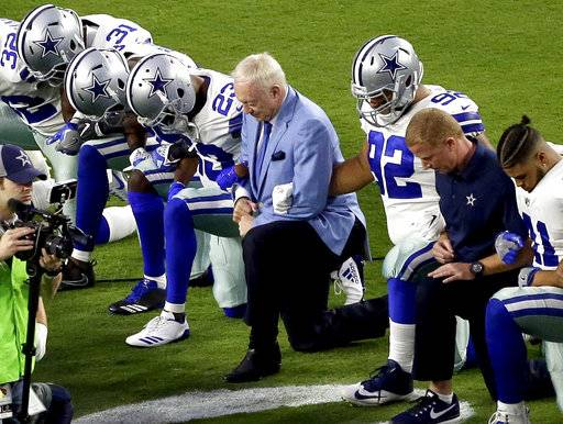 FILE - In this Monday, Sept. 25, 2017, file photo, the Dallas Cowboys, led by owner Jerry Jones, center, take a knee prior to the national anthem before an NFL football game against the Arizona Cardinals in Glendale, Ariz. What began more than a year ago with a lone NFL quarterback protesting police brutality against minorities by kneeling silently during the national anthem before games has grown into a roar with hundreds of players sitting, kneeling, locking arms or remaining in locker rooms, their reasons for demonstrating as varied as their methods.