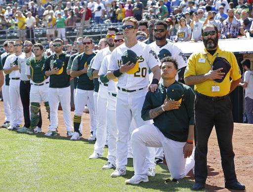 FILE - In this Sunday, Sept. 24, 2017, file photo, Oakland Athletics' Mark Canha (20) places his hand on the shoulder of Bruce Maxwell as Maxwell takes a knee during the national anthem prior to a baseball game against the Texas Rangers in Oakland, Calif. What began more than a year ago with a lone NFL quarterback protesting police brutality against minorities by kneeling silently during the national anthem before games has grown into a roar with hundreds of players sitting, kneeling, locking arms or remaining in locker rooms, their reasons for demonstrating as varied as their methods.