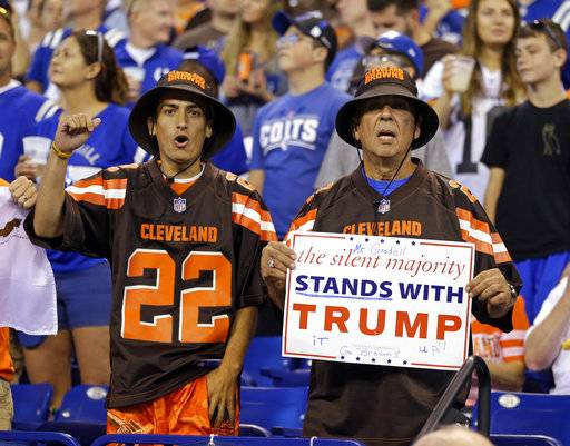 FILE - In this Sunday, Sept. 24, 2017, file photo, Cleveland Browns fans hold a sign following the national anthem before an NFL football game between the Indianapolis Colts and the Cleveland Browns in Indianapolis. What began more than a year ago with a lone NFL quarterback protesting police brutality against minorities by kneeling silently during the national anthem before games has grown into a roar with hundreds of players sitting, kneeling, locking arms or remaining in locker rooms, their reasons for demonstrating as varied as their methods.