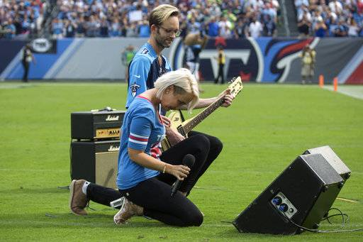 "FILE - In this Sunday, Sept. 24, 2017, file photo, Meghan Linsey, a former contestant on ""The Voice,"" kneels after singing the national anthem before the start of the Tennessee Titans and Seattle Seahawks football game at Nissan Stadium in Nashville, Tenn. What began more than a year ago with a lone NFL quarterback protesting police brutality against minorities by kneeling silently during the national anthem before games has grown into a roar with hundreds of players sitting, kneeling, locking arms or remaining in locker rooms, their reasons for demonstrating as varied as their methods.  (Ryan Hermens/The Paducah Sun via AP, File)"