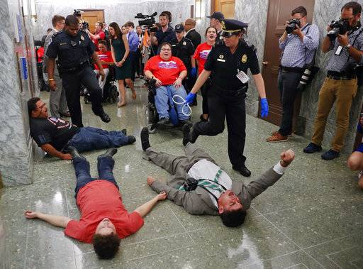 U.S. Capitol Police begin to detain protesters laying on the ground in an attempt to maintain order in the hallways outside the Senate Finance Committee hearing on the last-ditch GOP push to overhaul the nation's health care system, on Capitol Hill in Washington, Monday, Sept. 25, 2017. (AP Photo/Susan Walsh)