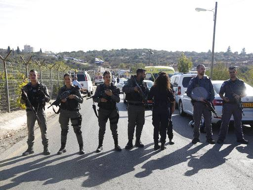 Israeli police blocks the road to Har Adar settlement near Jerusalem, Tuesday, Sept. 26, 2017. Israeli police said that a Palestinian attacker opened fire at the entrance to the settlement killing three Israeli men and critically wounding a fourth. (AP Photo/Mahmoud Illean)