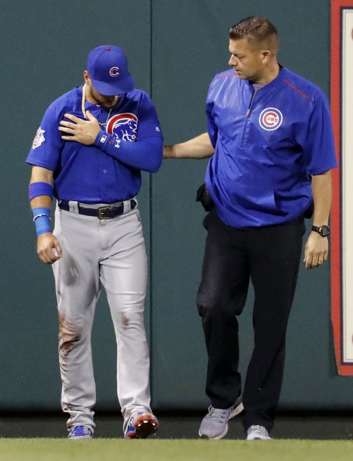 Chicago Cubs center fielder Albert Almora Jr. holds his shoulder as he is helped off the field by Cubs trainer PJ Mainville after slamming into the outfield wall chasing an RBI double by St. Louis Cardinals' Paul DeJong during the fifth inning of a baseball game Tuesday, Sept. 26, 2017, in St. Louis.