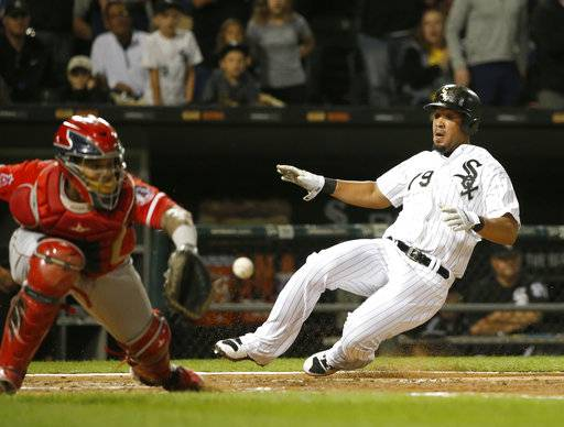 Chicago White Sox's Jose Abreu, right, scores past Los Angeles Angels catcher Martin Maldonado off a double by Nicky Delmonico during the fourth inning of a baseball game Wednesday, Sept. 27, 2017, in Chicago.