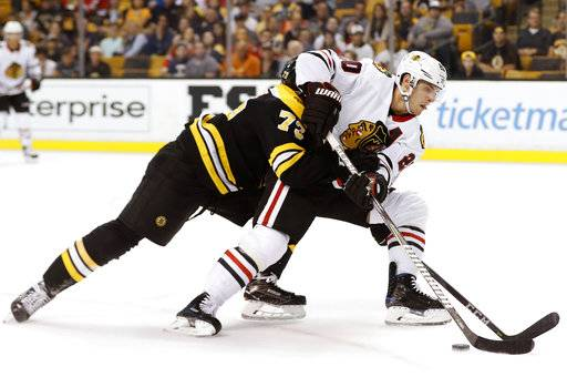 Chicago Blackhawks' Brandon Saad tries to get around Boston Bruins defenseman Charlie McAvoy during the first period of an NHL preseason hockey game in Boston, Monday, Sept. 25, 2017.