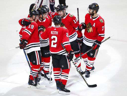 Chicago Blackhawks center Jonathan Toews (19) celebrates with teammates after scoring against the Columbus Blue Jackets during the third period of a preseason NHL hockey game Saturday, Sept. 23, 2017, in Chicago.