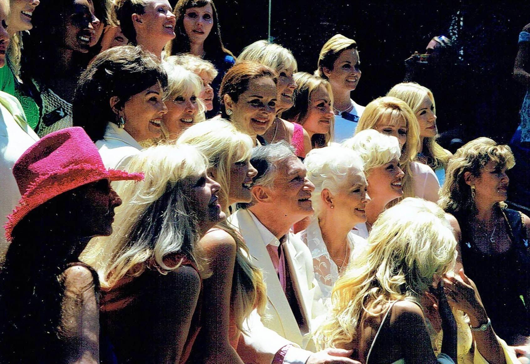 The late Hugh Hefner poses with 300 Playmates for Playboy magazine's 45th anniversary in this 1999 photo by James Bond novelist and Buffalo Grove writer Raymond Benson.