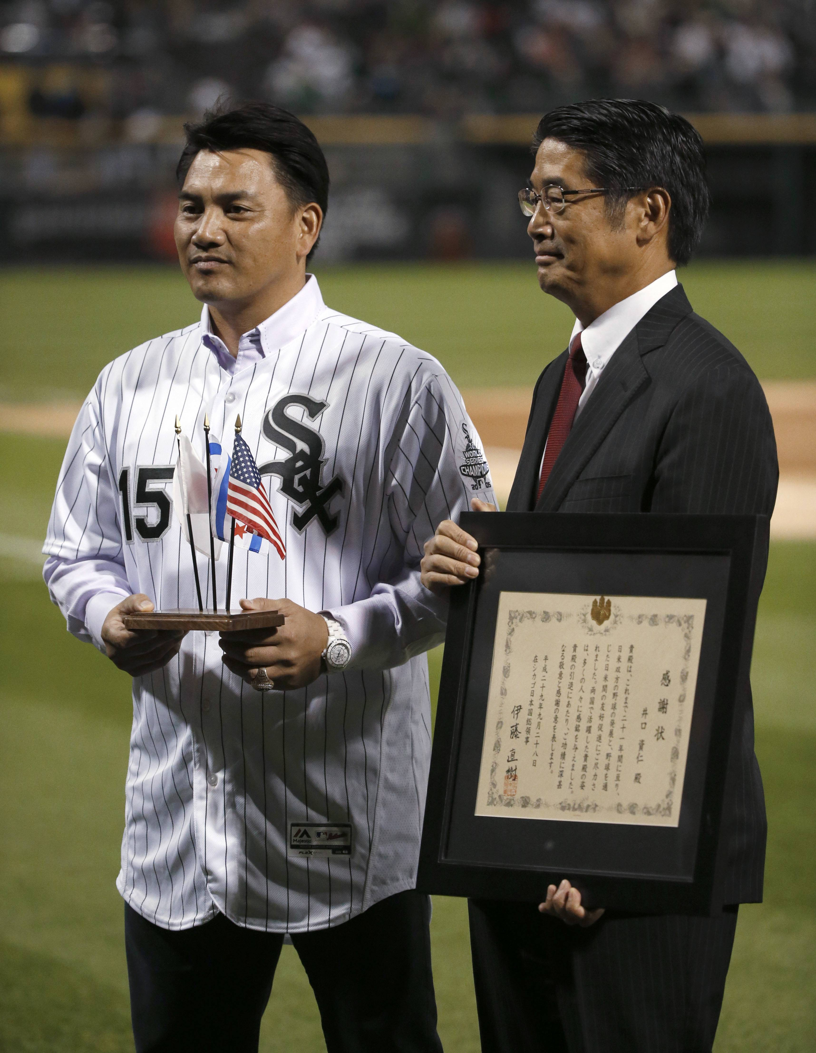 Former Chicago White Sox second baseman Tadahito Iguchi, left, is honored by Naoki Ito, consul-general of Japan in Chicago, during a ceremony before a baseball game between the White Sox and the Los Angeles Angels on Thursday, Sept. 28, 2017, in Chicago.