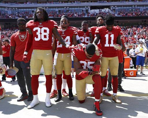"FILE - In this Sept. 10, 2017, file photo, San Francisco 49ers safety Eric Reid (35) kneels during the national anthem in front of teammates before an NFL football game against the and the Carolina Panthers in Santa Clara, Calif. The NFL says the message players and teams are trying to express is being lost in a political firestorm. NFL spokesman Joe Lockhart said Thursday, Sept. 28, 2017, that it is important for ""everyone to understand what they are talking about, to not see everything in terms of who is up or down politically."""
