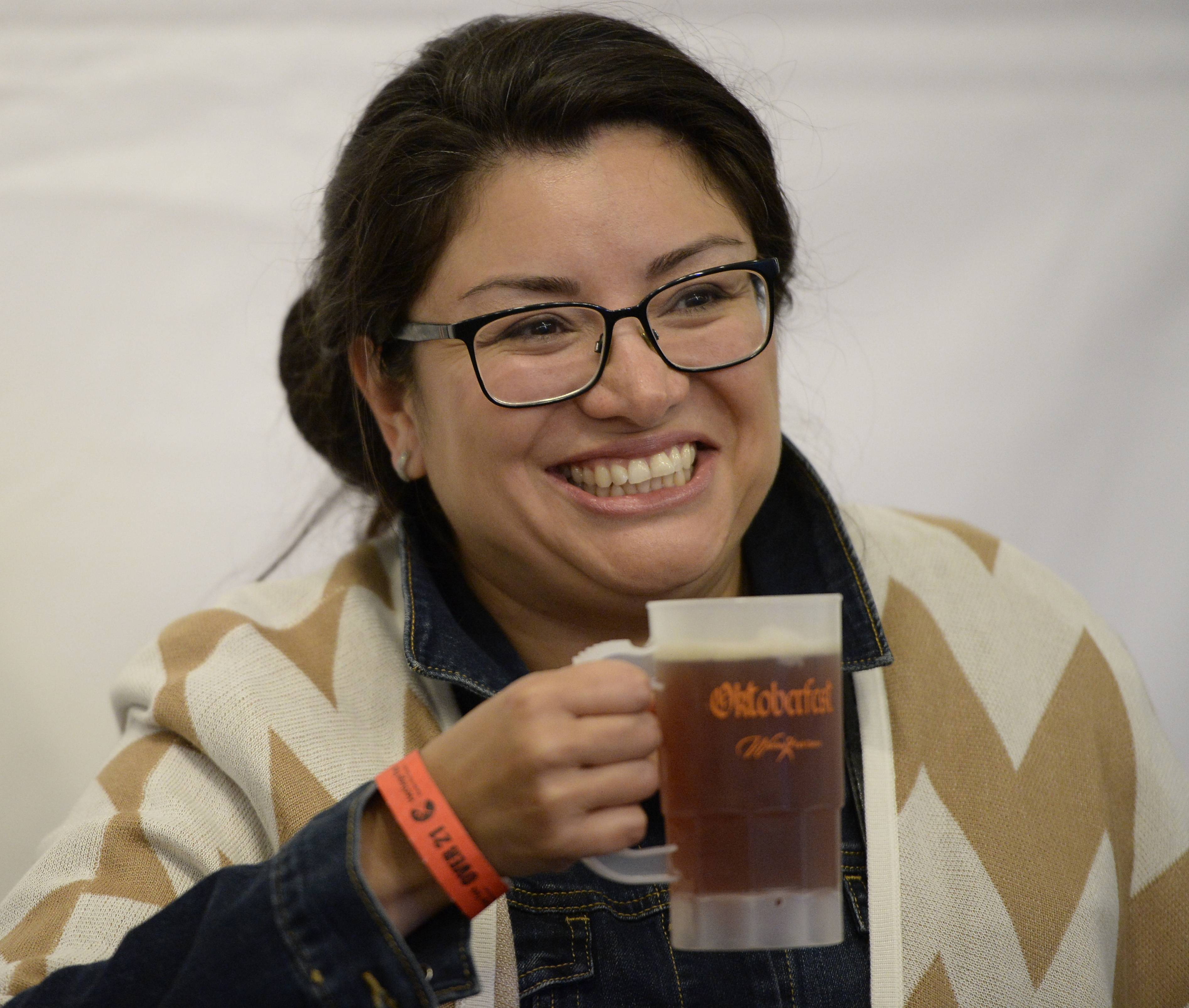 Evangelia Moreno of Wheeling enjoys the Oktoberfest brew at Heritage Park in Wheeling as she listens to the Modern Day Romeos perform on Friday evening.