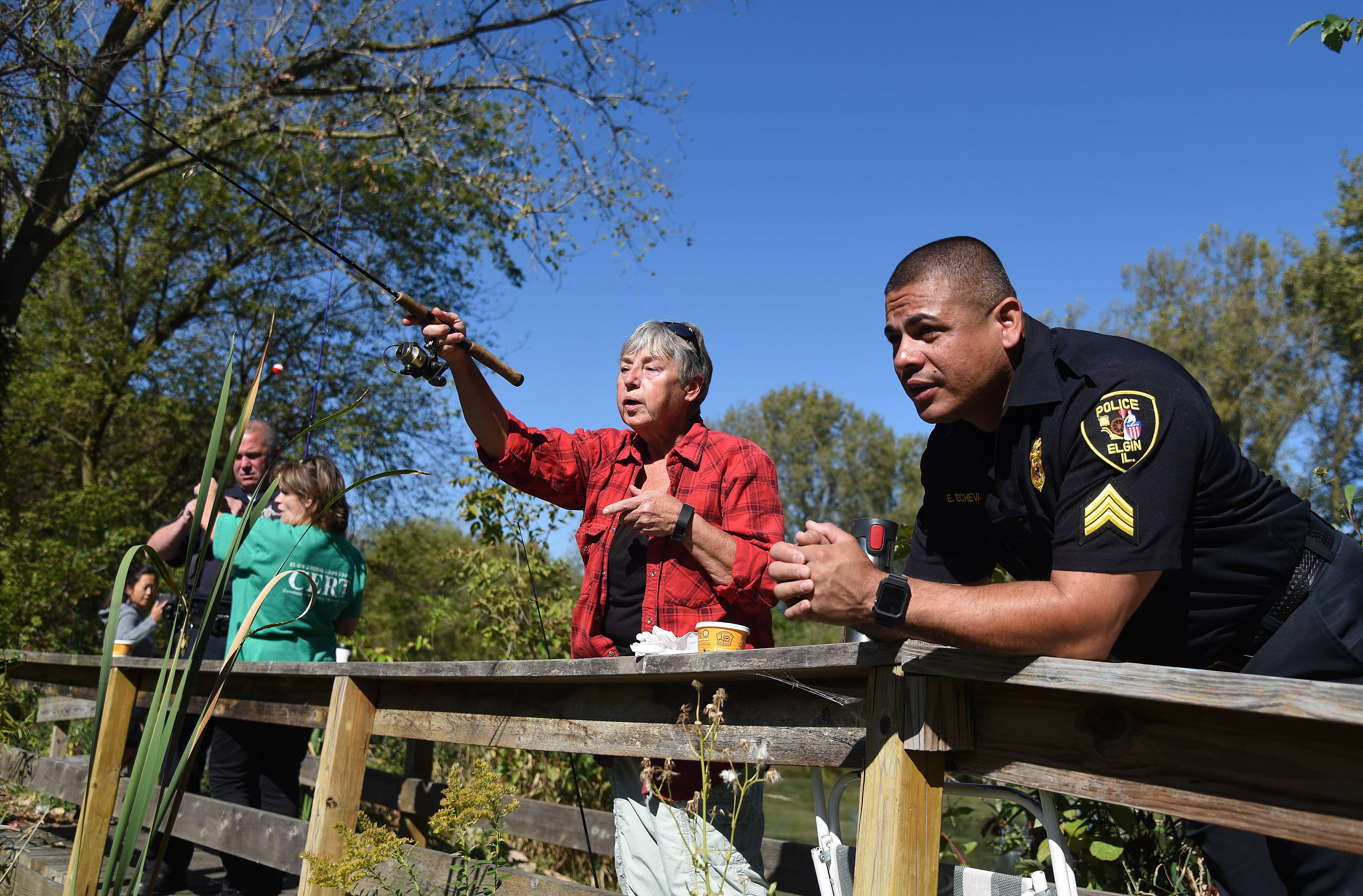 "Maxine Layton of Gilberts casts into a pond at Hawthorne Hills Nature Center in Elgin during a ""fishing with seniors"" event sponsored by the Elgin Police Department. Sgt. Eric Echevarria looks on."