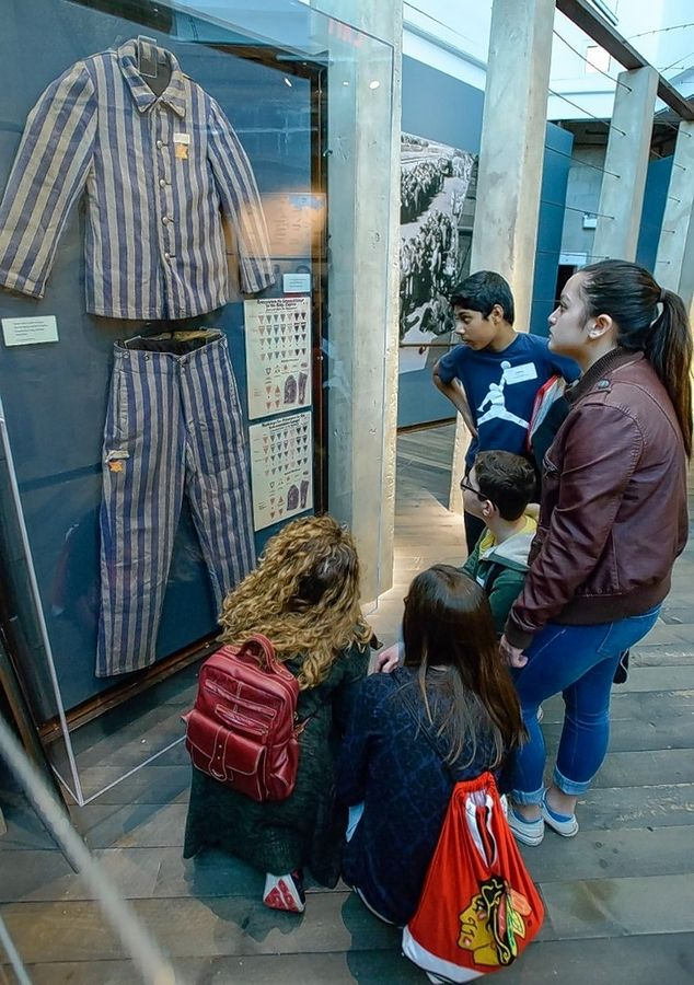 Students look at a concentration camp prisoner's uniform at the Illinois Holocaust Museum and Education Center in Skokie. A rise in anti-Semitism is being addressed by suburban religious leaders this Yom Kippur.