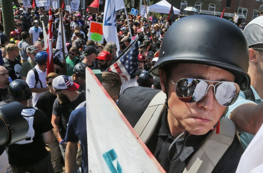 A white nationalist demonstrator with a helmet and shield walks into Lee Park in Charlottesville, Virginia, on Aug. 12. The anti-Semitism expressed during the rally is being addressed by suburban religious leaders this Yom Kippur