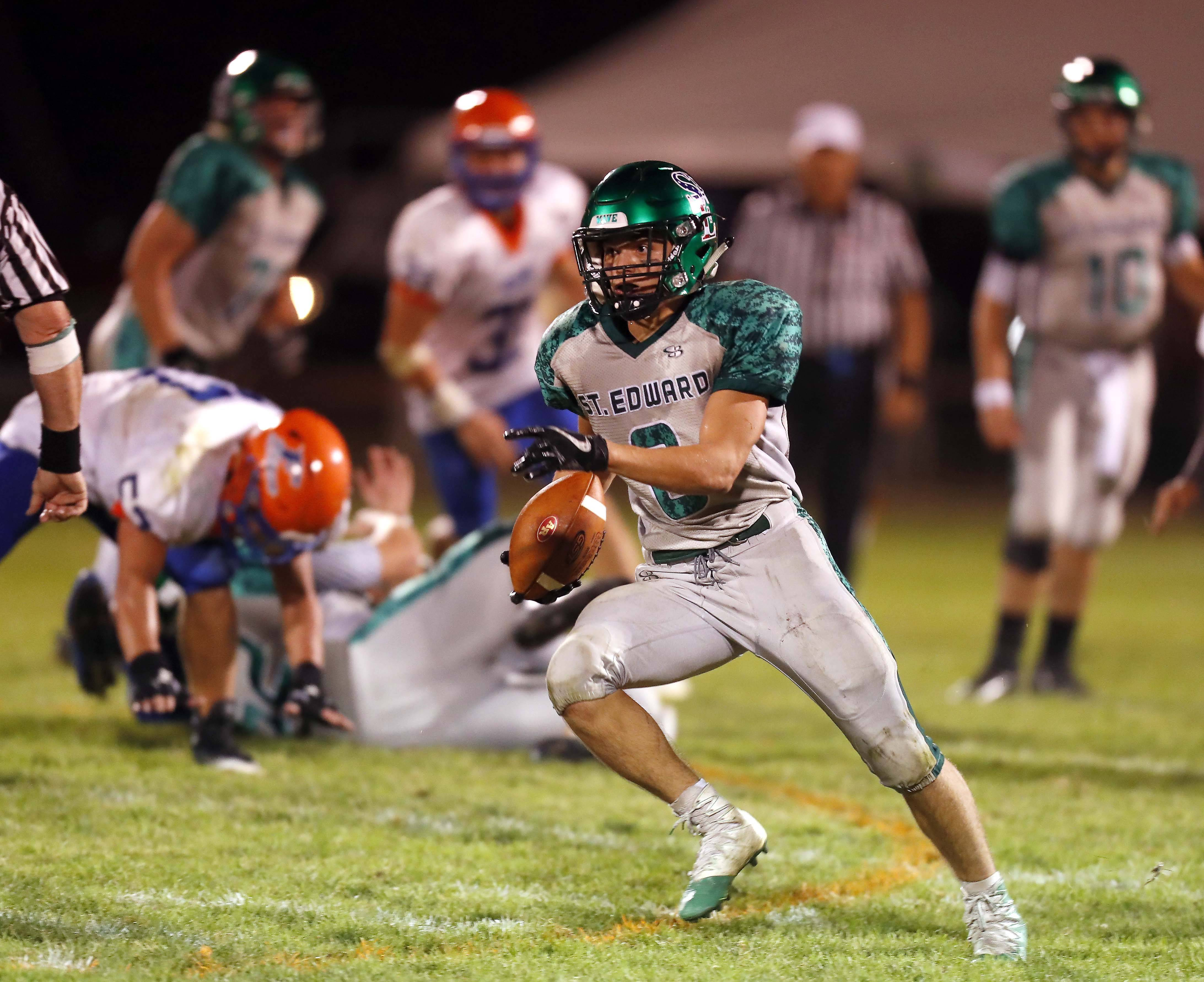 Brian Hill/bhill@dailyherald.com St. Edward's Nick Wright (8) moves up field for a long touchdown Friday during Fenton at St. Edward football at Greg True Field in Elgin.