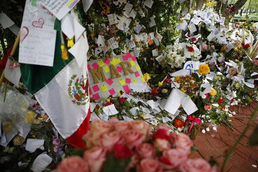 Flowers, handwritten messages, and a Mexican flag are arranged in a makeshift memorial for earthquake victims, erected by the community in Parque Mexico in the heart of the Condesa neighborhood of Mexico City, Friday, Sept. 29, 2017. On sidewalks, median strips and amid the brick dust, mud and rubble of the 38 buildings that collapsed in Mexico's 7.1 earthquake, impromptu memorials to victims and rescuers have sprung up, as the capital begins to come to terms with its losses. (AP Photo/Rebecca Blackwell)