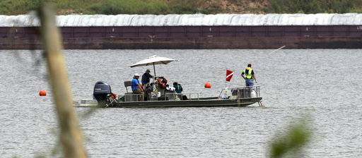 In this Sept. 13, 2017 photo, a boat with a dive flag is shown at San Jacinto River Waste Pits near the Interstate 10 bridge over the river in Channelview, Texas. The Environmental Protection Agency says an unknown amount of a dangerous chemical linked to birth defects and cancer may have washed downriver from a Houston-area Superfund site during the flooding from Hurricane Harvey. (AP Photo/David J. Phillip)