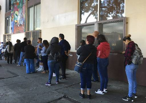 This Sept. 28, 2017 photo people wait in line at CHIRLA (Coalition for Humane Immigrant Rights Los Angeles) for help with immigration paperwork, including renewing work permits for expiring Obama-era program for immigrants brought to the country as children. After Oct. 5, 2017, no one else can renew under the program that has let nearly 800,000 immigrants brought to the United States as children work in the country even though they lack legal papers. (AP Photo/Amy Taxin)