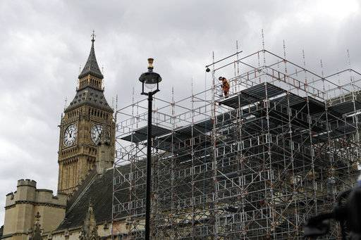FILE - A Monday, June 12, 2017, photo from files showing a man working on scaffolding on the Houses of Parliament in London, as scheduled renovation works continue. British authorities say the cost of repairing the tower that houses Big Ben have doubled. Parliamentary authorities said Friday the cost of repairing the Elizabeth Tower is now estimated to be 61 million pounds ($81 million.) It was previously estimated to be 29 million pounds. Authorities say the complexity of the project and scaffolding needed enable workers to reach heights safely resulted in increased costs. (AP Photo/Matt Dunham, File)