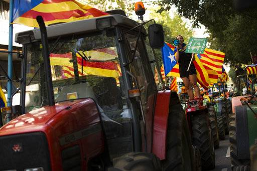 "A woman with the estelada, or Catalonia independence flags, shouts slogans on top of parked tractors during a protest by farmers in Barcelona, Friday, Sept. 29, 2017. Authorities in Catalonia aim to ensure that a disputed referendum on independence from Spain will take place peacefully on Sunday despite a crackdown on the vote by the national government, the region's interior chief said. The small placard read: ""Freedom"". (AP Photo/Francisco Seco)"