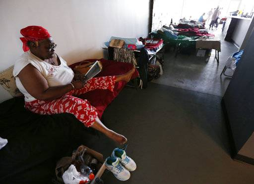 FILE- This Sept. 14, 2017 file photo, shows Helen Haynes reading at a special needs shelter at Florida International University in Miami, Fla. About 30 people, including staff with the Florida Keys Outreach Coalition for the Homeless from Key West, Fla., were sheltered in a storefront underneath a parking garage on campus.