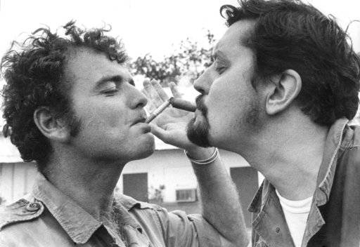 FILE - In this undated photo, Richard Pyle, AP Saigon bureau chief, right, and Rick Merron, AP photographer, light their cigarette and cigar at the Da Nang press camp during the Vietnam War. Pyle, an Associated Press reporter whose career spanned a half-century of war, catastrophe and other indelible stories has died in New York, Thursday, Sept. 28, 2017. Richard Pyle was 83.