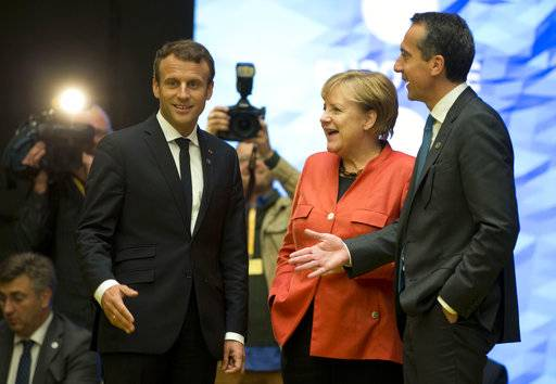 German Chancellor Angela Merkel, center, speaks with Austrian Chancellor Christian Kern, right, and French President Emmanuel Macron during a working session at an EU Digital Summit in Tallinn, Estonia on Friday, Sept. 29, 2017. The European Union is looking beyond its impending breakup with Britain at how to build a common future with the 27 nations remaining in the bloc. (AP Photo/Virginia Mayo)