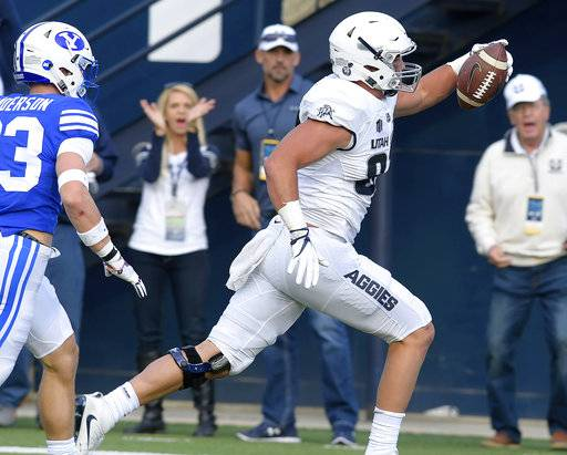 Utah State tight end Dax Raymond (87) celebrates as he scores a touchdown in front of BYU defensive back Zayne Anderson during an NCAA college football game, Friday, Sept. 29, 2017, in Logan, Utah. (Eli Lucero/Herald Journal via AP)