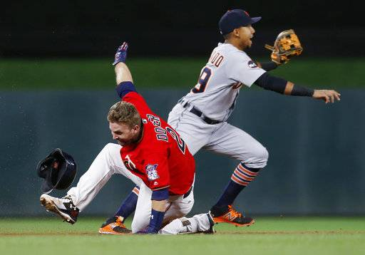 Minnesota Twins' Brian Dozier, left, stumbles after crossing second base as Detroit Tigers shortstop Dixon Machado waits for the throw on Dozier's double, during the first inning of a baseball game Friday, Sept. 29, 2017, in Minneapolis. Dozier made it back to second safely. (AP Photo/Jim Mone)