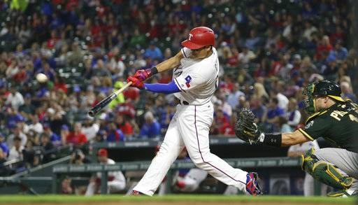 Texas Rangers designated hitter Shin-Soo Choo, left, of South Korea, hits a two-run home run in front of Oakland Athletics catcher Josh Phegley (19) during the fifth inning of a baseball game in Arlington, Texas, Friday, Sept. 29, 2017. Rangers' Drew Robinson also scored on the play. (AP Photo/LM Otero)