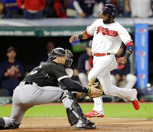 Cleveland Indians' Austin Jackson, right, scores as Chicago White Sox catcher Kevan Smith waits for the ball in the second inning of a baseball game, Friday, Sept. 29, 2017, in Cleveland.