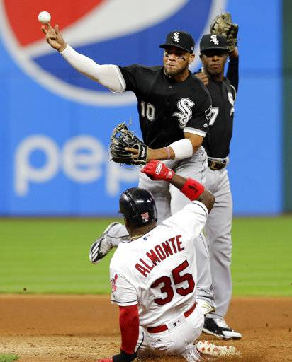Chicago White Sox's Yoan Moncada (10) throws to first base after getting out Cleveland Indians' Abraham Almonte (35) at second base in the seventh inning of a baseball game, Friday, Sept. 29, 2017, in Cleveland. Indians' Giovanny Urshela was out at first base for the double play. White Sox's Tim Anderson (7) watches the play.