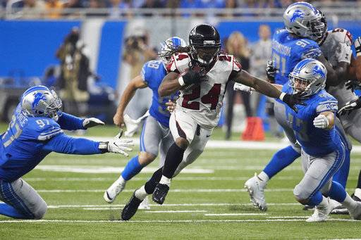 FILE - In this Sunday, Sept. 24, 2017, file photo, Atlanta Falcons running back Devonta Freeman (24) rushes against the Detroit Lions during an NFL football game in Detroit. Freeman isn't just quick with his feet for the Falcons. The NFL's highest-paid running back has exceptional field vision to read a defense and dart for extra yards. (AP Photo/Rick Osentoski, File)