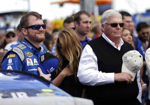 FILE - In this Feb. 21, 2016, file photo, Dale Earnhardt Jr, left, and team owner Rick Hendrick stand during the national anthem before the NASCAR Daytona 500 Sprint Cup Series auto race at Daytona International Speedway in Daytona Beach, Fla. Earnhardt Jr. said the views of two NASCAR team owners who said they would fire employees who do not stand for the national anthem does not speak for the sport. He said he hasn't discussed the issue with his teammates, crew or other employees at Hendrick Motorsports, but added that he will continue to stand for the anthem. (AP Photo/Chuck Burton, File)