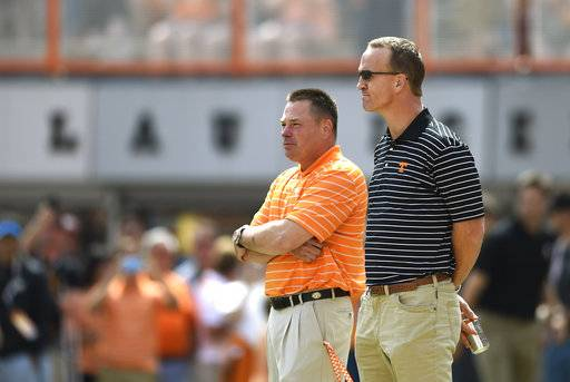 "FILE - In this April 25, 2015, file photo, Tennessee coach Butch Jones, left, and former Tennessee quarterback Peyton Manning, watch players warm up before the NCAA college football team's Orange & White game at Neyland Stadium in Knoxville, Tenn. Manning says he's ""pulling hard� for Volunteers coach Butch Jones, who has received perhaps the toughest criticism of his five-year tenure over the last couple of weeks. (Adam Lau/Knoxville News Sentinel via AP, File)"