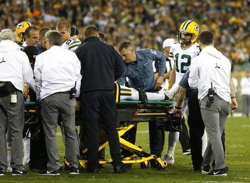 Green Bay Packers' Aaron Rodgers watches as teammate Davante Adams is taken off the field after being hit in the head during the second half of an NFL football game against the Chicago Bears Thursday, Sept. 28, 2017, in Green Bay, Wis.