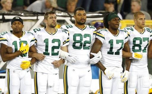 Green Bay Packers link arms during the national anthem before an NFL football game against the Chicago Bears Thursday, Sept. 28, 2017, in Green Bay, Wis.