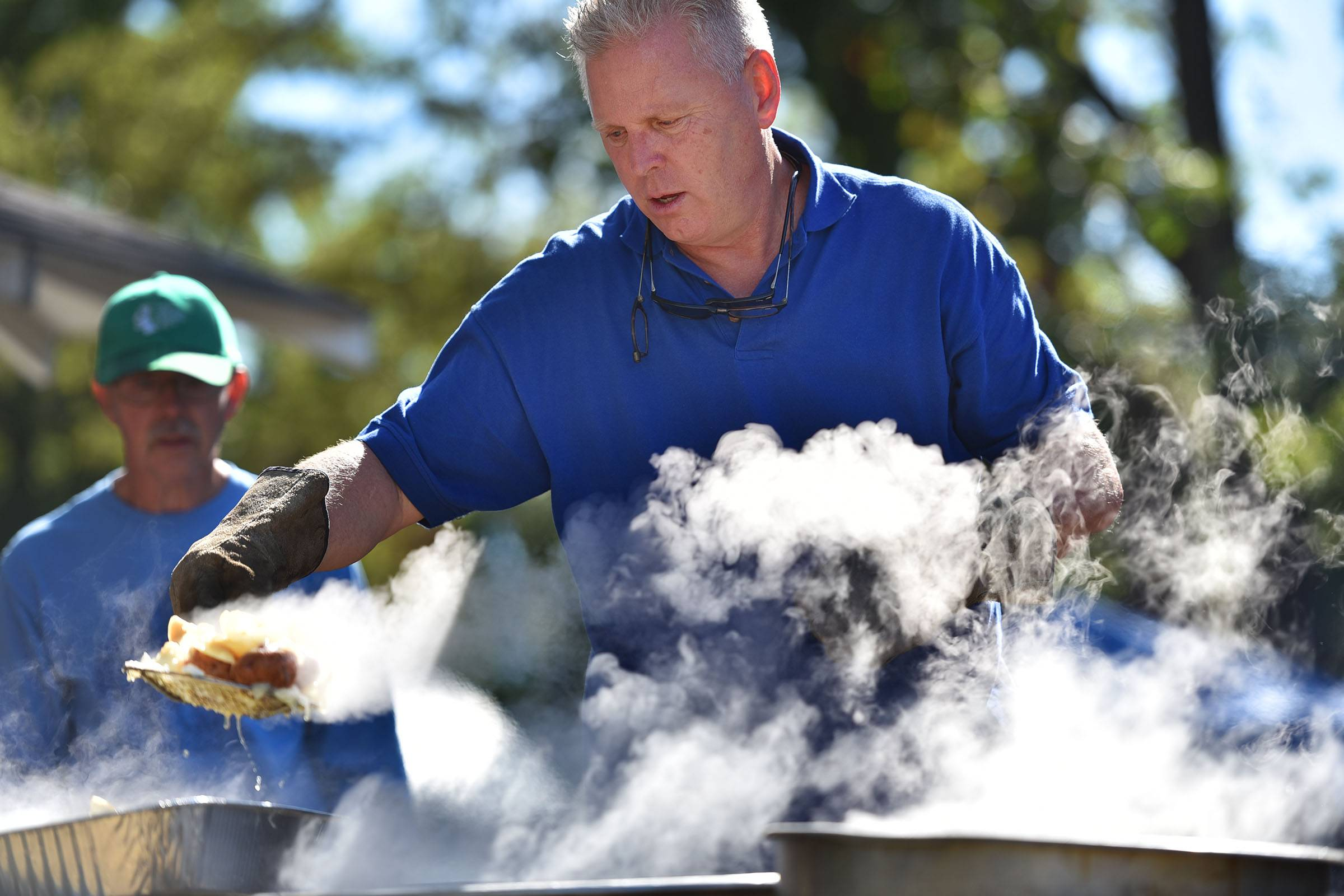 As steam rises, David Anthonsen scoops Icelandic cod with potatoes and onions from boiling pots over an open fire pit at the 17th Fish Boil at Vasa Park in South Elgin Saturday.