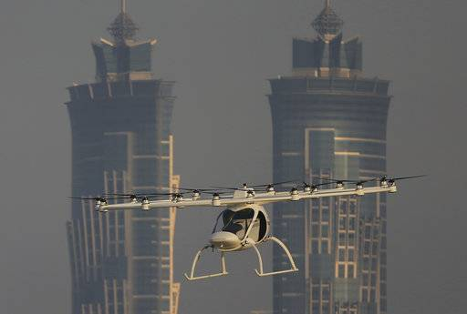 In this Sept. 26, 2017 photo, a Volocopter prototype flies in front of the two hotel towers during a test flight in Dubai, United Arab Emirates. Dubai is hoping to one day have flying, pilotless taxis darting among its skyscrapers. Just this week, the city-state in the United Arab Emirates hosted crews from the German company Volocopter, which had an electric, battery-powered two-seat prototype take off and land. Dubai hopes to have rules in place in the next five years to be ready for having the aircraft regularly flying through its skies.