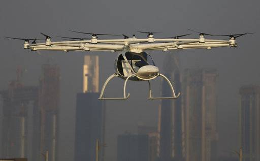 In this Sept. 26, 2017 photo, a Volocopter prototype flies in front of the city skyline during a test flight in Dubai, United Arab Emirates. Dubai is hoping to one day have flying, pilotless taxis darting among its skyscrapers. Just this week, the city-state in the United Arab Emirates hosted crews from the German company Volocopter, which had an electric, battery-powered two-seat prototype take off and land. Dubai hopes to have rules in place in the next five years to be ready for having the aircraft regularly flying through its skies.