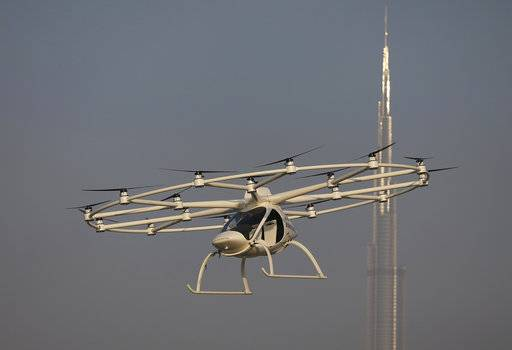 In this Sept. 26, 2017 photo, a Volocopter prototype flies in front of the Burj Khalifa, the world's tallest tower, during a test flight in Dubai, United Arab Emirates. Dubai is hoping to one day have flying, pilotless taxis darting among its skyscrapers. Just this week, the city-state in the United Arab Emirates hosted crews from the German company Volocopter, which had an electric, battery-powered two-seat prototype take off and land. Dubai hopes to have rules in place in the next five years to be ready for having the aircraft regularly flying through its skies.