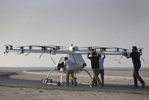 In this Sept. 26, 2017 photo, a Volocopter prototype is being pushed by their operators before it sets for a test fly in Dubai, United Arab Emirates, Tuesday, Sept. 26, 2017. Dubai is hoping to one day have flying, pilotless taxis darting among its skyscrapers. Just this week, the city-state in the United Arab Emirates hosted crews from the German company Volocopter, which had an electric, battery-powered two-seat prototype take off and land. Dubai hopes to have rules in place in the next five years to be ready for having the aircraft regularly flying through its skies.