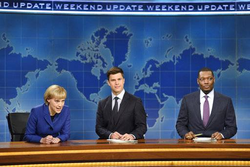 "In this image released by NBC, Kate McKinnon portraying German Chancellor Angela Merkel, left, appears with Weekend Update hosts Colin Jost, center, and Michael Che during their segment on ""Saturday Night Live,"" in New York on Sept. 30, 2017. (Will Heath/NBC via AP)"