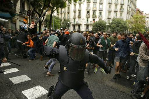 Spanish riot police swings a club against would-be voters near a school assigned to be a polling station by the Catalan government in Barcelona, Spain, Sunday, Oct. 1, 2017. Spanish riot police have forcefully removed a few hundred would-be voters from several polling stations in Barcelona.